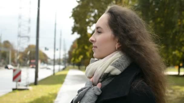 Mladá dáma čeká na někoho v krásný podzim v parku