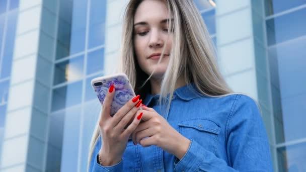 Krásná dáma s použitím její mobilní telefon, smarthone, textilie před moderním městském architektura