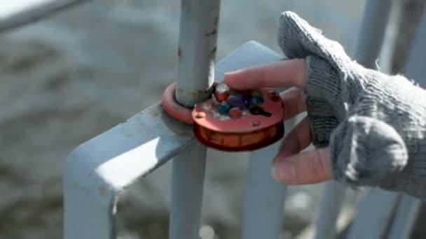 Zámky lásky na zrezivělé kovové zábradlí na břehu řeky Daugava v Rize