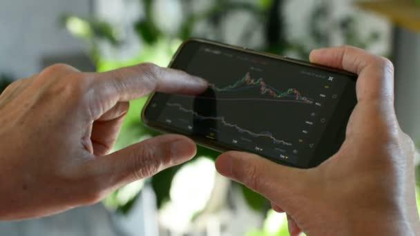 Bitcoin piac, crypto kereskedési online, kereskedő dolgozik a mobiltelefon cryptovalutaváltó. Ember megható képernyő, böngészés piaci adatok, chart. Kriptográfiai pénznem. Bitcoin-cryptocurrency.