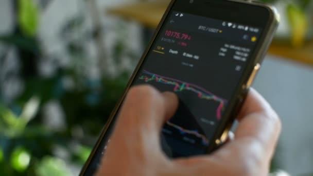 Trh s bitmincemi, kryptografické obchodování online, obchodník pracující s mobilním telefonem na výměnu Kryptoměny. Člověk se dotýká obrazovky, prohlížeje data na trhu, graf. Kryptografická měna Bitminově kryptoměna.