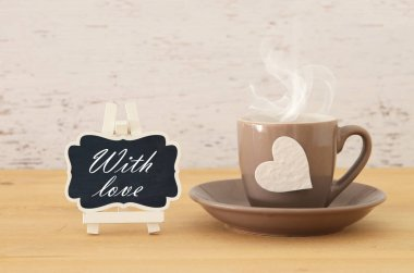 image of coffe cup with heart over wooden table