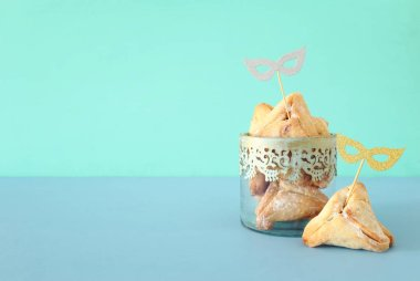 Purim celebration concept (jewish carnival holiday). Traditional hamantaschen cookies with cute gold masks over blue wooden table