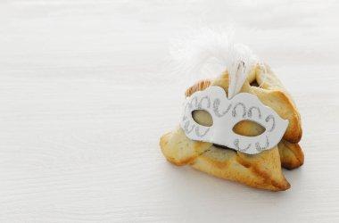 """Картина, постер, плакат, фотообои """"концепция празднования пурим (еврейский карнавал). традиционное печенье хаманташен с милой маской на белом деревянном столе """", артикул 241650918"""