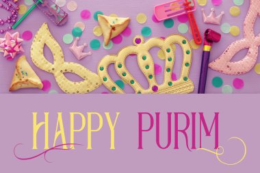 Purim celebration concept (jewish carnival holiday) over wooden pink background