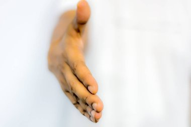 Close up businessmen hands stretched out for handshaking. Businessman or salesman, stretches his hand to conclude a business deal. Partners welcoming after negotiation of contract or agreement complete.