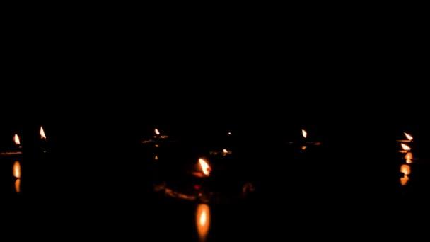 diya- Lampen beleuchtet in der Festival-Saison von diwali. Gruppe brennender Öllampen auf schwarzem Hintergrund. Kerzen, die im Dunkeln mit echter roter Flamme entzündet werden. Kopierraum für Text nach oben.