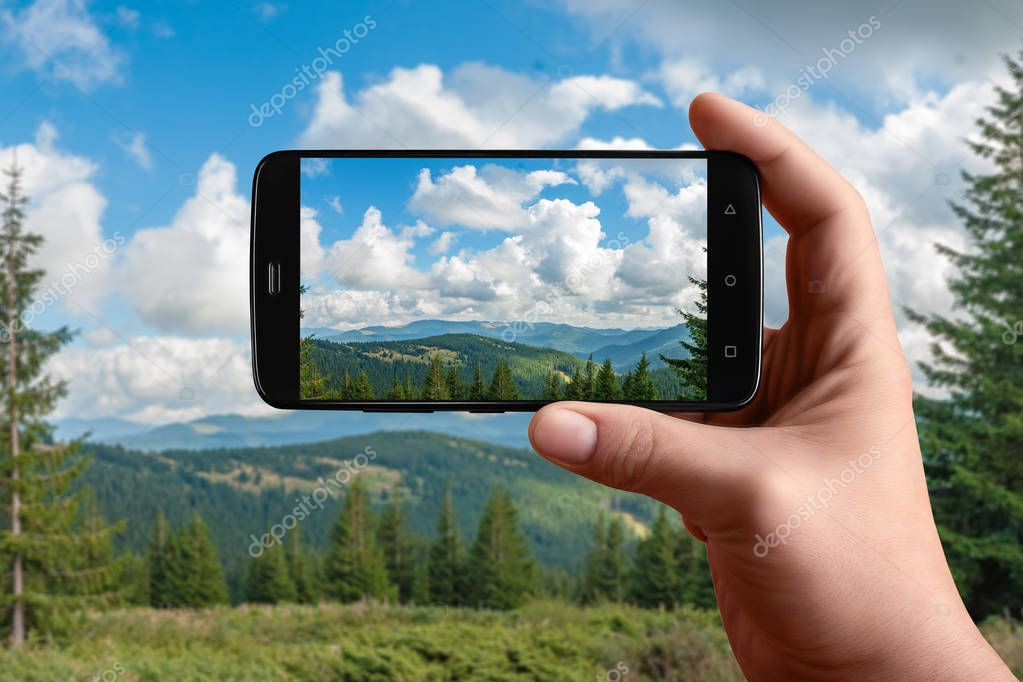 Smartphone in hand photographs nature on the screen. Photos of the mountain panorama for posting on social networks.