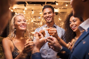 Group of multiethnic friends having fun with sparkling sticks during night party. Group of elegant women and men holding sparkler and celebrating the new years eve. Smiling guys and women having fun at night with firework sticks.