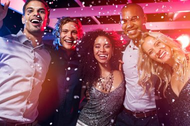 Happy young friends dancing at party night with confetti. Group of beautiful women and elegant men dancing together and looking at camera while partying in nightclub. Group of smiling multiethnic people celebrating.