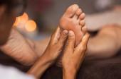Fotografia Closeup of masseuse doing foot reflexology to woman at spa. Therapist hands doing foot massage at wellness center. Woman receiving a feet massage at health spa.