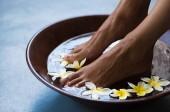 Fényképek Nő, láb tál vízben úszó frangipáni virágok Spa áztatás. Vértes egy női láb pedikűr eljárásról szóló wellness-központban. Nő láb spa fából készült tál egzotikus fehér virágok