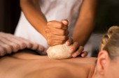 Closeup of masseuse hands holding cloth giving pinda massage to woman on spa table. Therapist hands giving ayurveda aroma pinda sweda massage to naked lady. Senior woman doing aromatic painkiller massage on back.