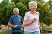 Starší pár běh venku v parku. Starší muž a žena společně zaběhat. Bývalý muž a aktivní žena použití venkovní.