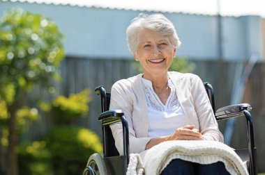 Happy senior woman sitting on wheelchair and recovering from illness. Handicapped mature woman sitting in wheelchair smiling and looking at camera. Portrait of a disabled elderly woman outdoor in a nursing home.
