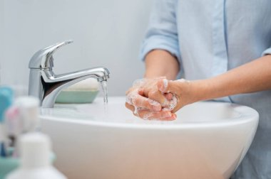 Closeup of woman applying soap while washing hands in basin with open tap. Mature woman washing hands for cleanliness purpose. Lady rubbing hands filled with soap.
