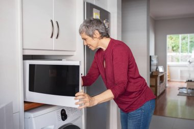Senior woman keeping food in oven for heating. Mature woman opening microwave oven in kitchen at home for cooking. Housewife cooking with a microwave in modern kitchen.