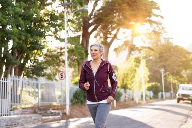 Smiling senior woman jogging on streets in early morning. Active mature woman running on a sunny day while listening to music. Lady running with armband and listening to music with earphones at sunset.