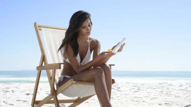 On Applying Deckchair With Sitting And Young CameraSmiling Woman Copy Tanned In White Girl SpaceBeautiful At Sunscreen Bikini Latin Beach Suntan Looking Lotion While YgyIbvf76