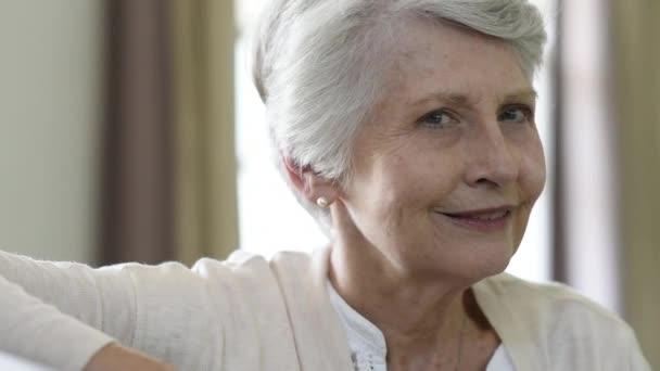 Usměvavá starší žena odpočinku na gauči doma a při pohledu na fotoaparát. Portrét starší ženy sedí na pohovce. Closeup veselá babička relaxační krytý.