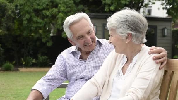 Starší pár společně sedí na lavičce v parku. Starší manželský pár sedí venkovní a relaxační. Romantický manžel obejmout svou ženu při pohledu daleko a s úsměvem. Koncept budoucnosti a odchod do důchodu.