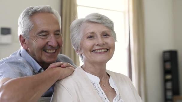 Boldog egészséges vezető pár otthon portréja. Romantikus régi pár ül együtt a kanapé mellett látszó-nél fényképezőgép. Vidám idős feleség és a férj élvezi élet-a nyugdíj után.