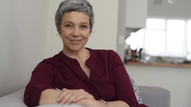 Porträt einer lächelnden Seniorin, die es sich zu Hause auf der Couch gemütlich macht. glückliche reife Frau, die auf dem Sofa sitzt und in die Kamera schaut. Nahaufnahme einer Dame, die sich zu Hause entspannt.