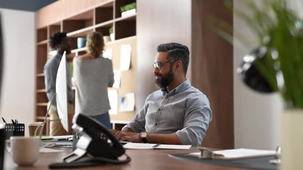 Happy middle eastern businessman relaxing in his office while looking computer monitor. Smiling mature business man with beard and eyeglasses sitting with hands behind head at office desk. Relaxed casual man taking a break at workplace.