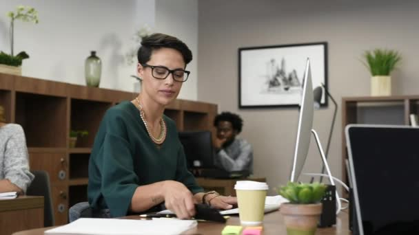Happy fashionable girl using smartphone while working on desktop computer. Cheerful young business woman sitting in coworking space typing on smart phone and looking at camera. Portrait of beautiful glamour freelancer with eyeglasses working.