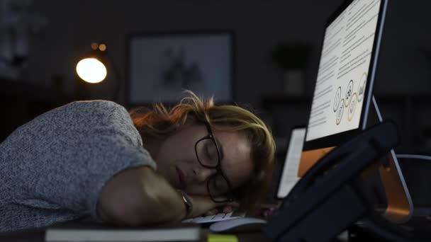 Zralé ženy nosí brýle, naklonil se a spí na klávesnici počítače v kanceláři. Detail tváře unavené podnikatelka dělá přesčasy spát na ploše se obrazovka zobrazení prezentace. Portrét ospalý blondýnka v tmavé kanceláři