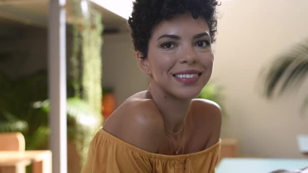 Portrait of african american woman looking at camera at coffee shop. Happy brazilian girl smiling indoor. Close up face of beautiful black girl with an afro hairstyle looking at camera.