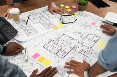 Closeup of multiethnic hands on blueprints at architects office. Team of designer and engineers working together on new residence complex. Top view of blue prints layout of house and buildings on wooden table.