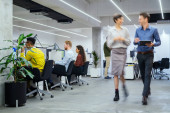 Skupina podnikatelů pracujících v kreativní kanceláři. Interiér zaneprázdněných zaměstnanců ve spolupracujícím prostoru. Firemní podnikatelé a podnikatelky sedí u stolů a procházejí se v práci.