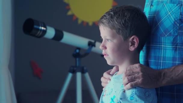 Kleiner Junge und alter Mann stehen in der Nähe des Fensters und zeigen auf den Kometen. Glücklicher Enkel, der nachts mit dem Opa Sternschnuppen beobachtet. Kind zeigt Opa vor dem Fenster etwas an und betrachtet ihr helles Zukunftskonzept.