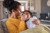 Schwarze Mutter hilft kranker Tochter beim Vernebeln, während sie sie zu Hause auf der Couch umarmt. Frau inhaliert indisches Mädchen mit Geräten. Krankes Kind auf Couch liegend mit Atemwegserkrankung, Hilfe von liebenswerter Mutter.