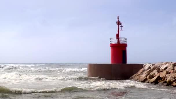 Aktuální mořské vody a vlny na přístav přístup s červenými lighthouse tower pohledu ze skály wave bezpečnostní bariéry.
