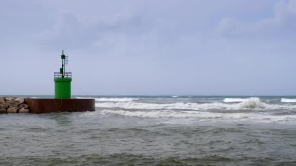 Meer Strömung und Wellen auf einem Port-Zugriff mit grünen Leuchtturm angesehen von den Felsen der Welle Sicherheitsschranke