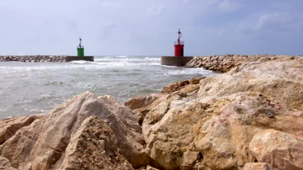 Sea water current and waves on a harbor access with green lighthouse tower viewed from the rocks of a wave safety barrier.