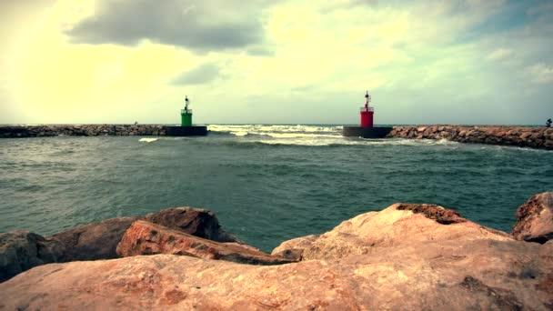 Aktuální mořské vody a vlny na přístav přístup s věží zelený maják pohledu ze skály wave bezpečnostní bariéry.