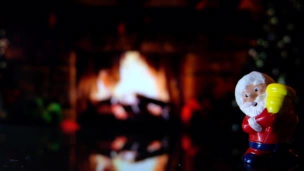 Mikulás játék kandallóval és egy meleg nappali háttérben éjjel karácsonyfa. 4k klip felvételeket kész hurok karácsonyfa átlátszó labda, vagy a csecsebecse az Üdvözlet szöveggel boldog karácsonyt és boldog új évet