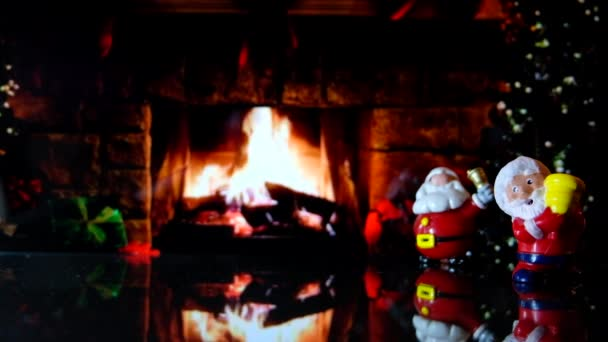 Couple of Santa Claus toys with fireplace and Christmas tree in a warm  living room background at night  4k clip footage ready for loop with  Christmas tree transparent ball or bauble with the greetings