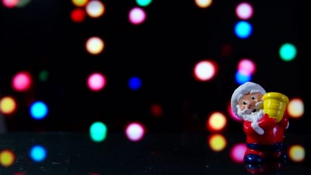 Santa Claus hračka s vánoční barevné osvětlení rozostřeného pozadí v noci. 4k oříznutí záběru připravena na smyčku s transparentní koule vánoční stromeček nebo cetka s uvítací text Veselé Vánoce a šťastný nový rok.