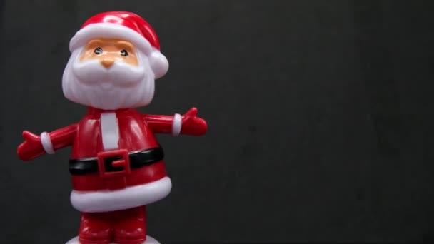 Santa Claus Bobblehead, právo kopírovat prostor. 4k oříznutí záběru připravena smyčka na černém pozadí s transparentní koule vánoční stromeček nebo cetka s uvítací text Veselé Vánoce a šťastný nový rok.