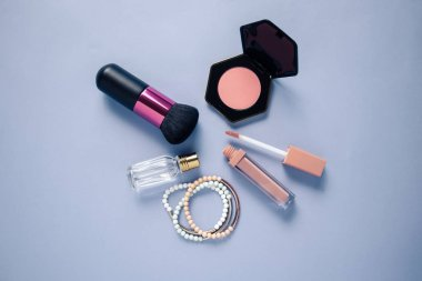 Brush, pink blush, lipstick, perfume and accessories on a flat lay. Beauty background.