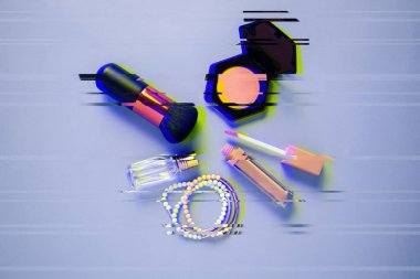 Brush, pink blush, lipstick, perfume and accessories on a flat lay. Glitch effect.