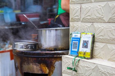 Qr codes for cashless payment with smart phones stands over a take-away booth in Shenzhen, China. Digitalization, such as cashless payment, in daily life is being widely accepted.