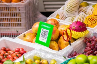 Qr codes for cashless payment with smart phones stands at a fruit street booth in Shenzhen, China. Digitalization, such as cashless payment, in daily life is being widely accepted.