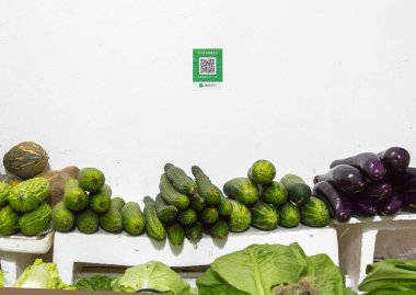 Qr codes for cashless payment with smart phones stands over a vegetable booth in Shenzhen, China. Digitalization, such as cashless payment, in daily life is being widely accepted.
