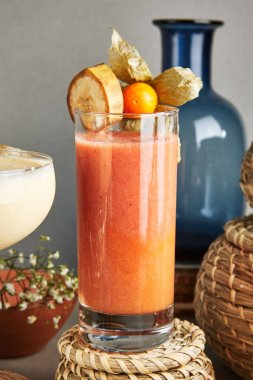 Fresh Homemade Fruit Smoothie with Banana, Physalis, Raspberry, Mango and Strawberry. Refreshment Fruits and Berries Iced Shake, Vitamin Detox Cocktail with Natural Juice on Rustic Background