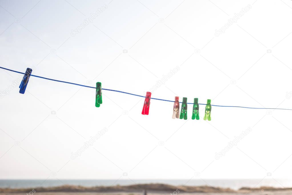 multicolored clothespins on a leash outdoors on the sky background
